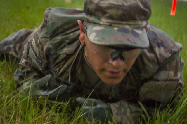 """A U.S. Army Soldier, assigned to Multinational Battle Group-East's Forward Command Post, crawls through an obstacle course during a spur ride on Camp Bondsteel, Kosovo, June 3. The Soldiers endured the mud and rain, performing a series of grueling mental and physical tasks, in order to be inducted into the Cavalry's """"Order of the Spur."""""""