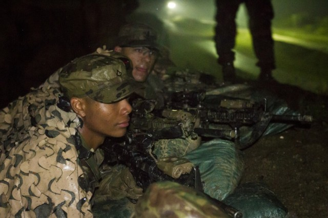 """U.S. Army Soldiers, assigned to Multinational Battle Group-East's Forward Command Post, construct hasty fighting positions during a spur ride on Camp Bondsteel, Kosovo, June 3. The Soldiers endured the mud and rain, performing a series of grueling mental and physical tasks, in order to be inducted into the calvary's """"Order of the Spur."""""""