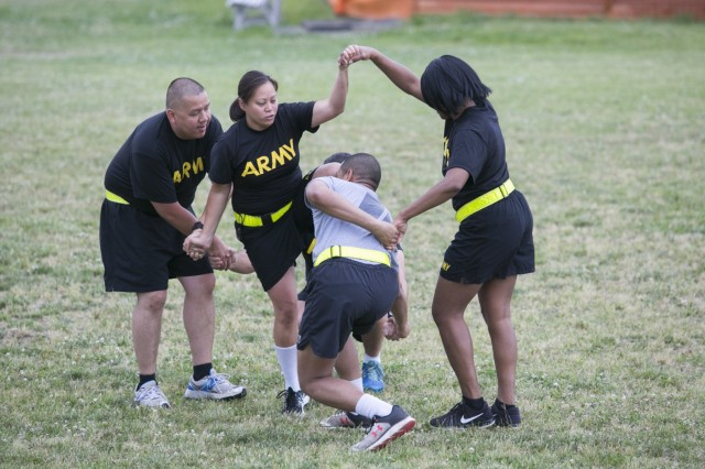 Camp Zama Soldiers work together to untangle themselves for a human knot activity June 9 during a field day hosted by the 78th Signal Battalion for the Female Enrichment Mentorship Program's day of teaming up to empower women. (U.S. Army photo by Honey Nixon)
