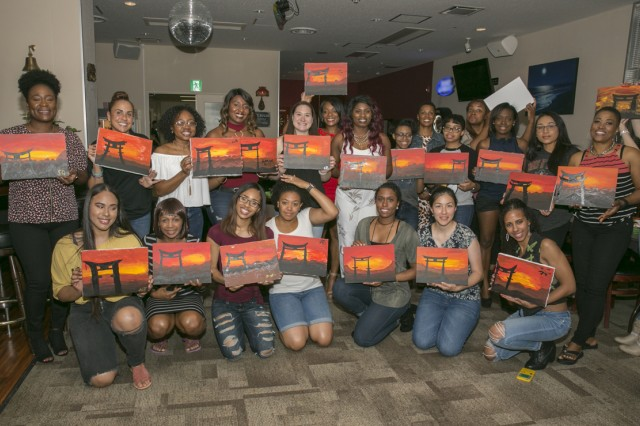 Participants pose with their paintings June 9, 2017 after the Sip and Paint Event for Camp Zama's Female Enrichment Mentorship Program in the Sagamihara Family Housing Area Club. (U.S. Army photo illustration by Honey Nixon)