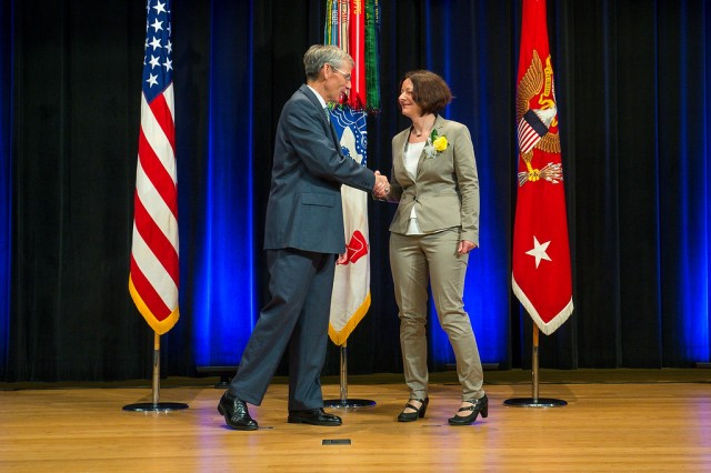 Acting Secretary of the Army the Honorable Robert M. Speer (left) presents Eva-Maria Ackermann with the Army's 'Editor of the Year' award during a ceremony in the auditorium of the Pentagon in Arlington, Virginia, June 6. Ackermann works for U.S. Army Europe in Wiesbaden, Germany.