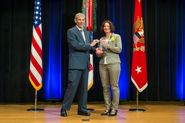 Acting Secretary of the Army the Honorable Robert M. Speer (left), and Eva-Maria Ackermann, at an awards ceremony in the auditorium of the Pentagon in Arlington, Virginia, June 6. Ackermann was named the Army's 'Editor of the Year.' She works for U.S. Army Europe in Wiesbaden, Germany.