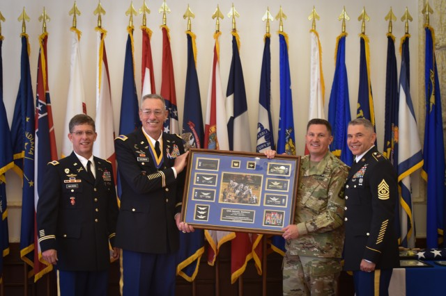 Pictured from left to right, Col. Chistopher Waters, the commander of 12th Combat Aviation Brigade, Chief Warrant Officer 5 Mike Sherman, Chief Warrant Officer Mike Boley, and Command Sgt. Maj. Osvaldo Martell.  Sherman received his retirement gift during a retirement ceremony hosted by the 12th CAB on Katterbach Army Airfield, Jun. 14, 2017.  Sherman served for 41 years in the U.S. Army and his time includes five combat deployments, four years as an enlisted 11E Armor Crewman, two years as a UH-1h Huey pilot, and 35 years as a CH-47 Chinook pilot.