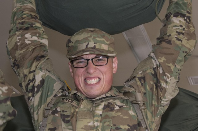 A Soldier in Training with Alpha Company, 3rd Battalion, 13th Infantry Regiment grimaces as he struggles to hold his duffle bag above his head June 6. The unit was one of the first to pick up larger cycles due to the summer surge in Basic Combat Training.