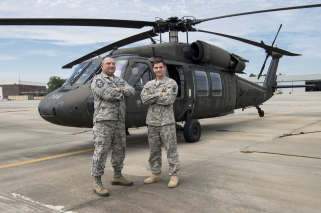 U.S. Army 2nd Lt. Michael Snyder with A Co. 1-111th General Support Aviation Battalion, right, and U.S. Air Force Senior Master Sgt. Edward Snyder with the 169th Fighter Wing pose for a photograph at McEntire Joint National Guard Base in Eastover, South Carolina, June 13, 2017.