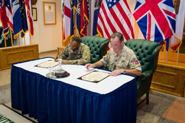 Brig. Gen. Kevin Vereen, U.S. Army Military Police School commandant, and Brigadier David Neal, provost marshal of the British Army's Royal Military Police, sign the Bond of Friendship declaration Tuesday.