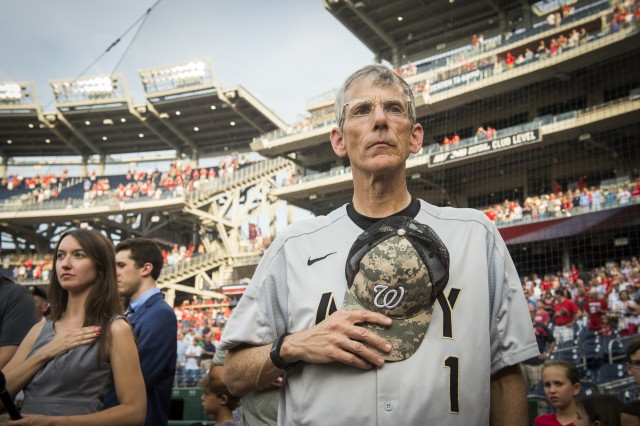 Acting Secretary of the Army Robert M. Speer stand with his hand over his heart during the National Anthem of this year's U.S. Army Day at the Nationals Park, Washington D.C., June 13, 2017.