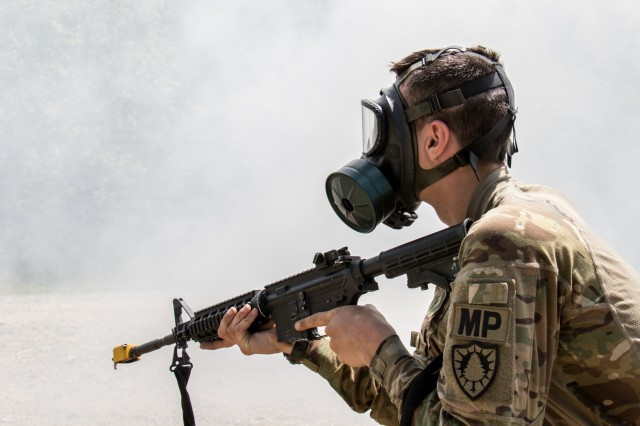 Spc. Dakota McGraw from the 488th Military Police Company wears his gas mask as his squad is surrounded by a mock toxic gas cloud during the unit's annual training at Plymouth Training Site.  The training lasted over a week during which they conducted events such as vehicle recovery, patrolling, security measures, Humvee operations, and vehicle maintenance.  The training was also host to their annual event, the Best Military Police Squad Competition.  This put nine squads from the unit head to head in a physical and mental test lasting 12 hours.  The competition tested each squads physical training, ruck march ability, medical skills, radio communication proficiency, and much more.