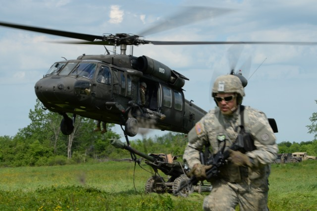 A New York  Army National Guard Soldier from 1st Battalion, 258th Field Artillery, runs from a UH-60 Black Hawk helicopter on Fort Drum, N.Y., June 9, 2017. The Soldier had helped hook up a M119A2 howitzer to the Black Hawk and was making his way back to the rest of his team.