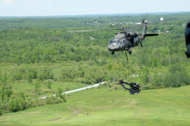 A New York Army National Guard UH-60 Black Hawk Helicopter transports a M119A2 howitzer over Fort Drum, N.Y., June 8, 2017. Soldiers from 1st Battalion, 258th Field Artillery were conducting annual training, which involved setting up Howitzers, firing, then extracting them.