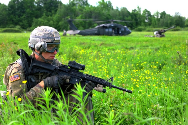 FORT DRUM, N.Y. -New York Army National Guard Pfc. Michael Natole, a cannon crewmember assigned to Alpha Battery, 1st Battalion, 258th Artillery Regiment, 27th Infantry Brigade Combat Team, stands watch during an air assault artillery raid at Fort Drum on June 9, 2017. During the raid 4 of the battery's howitzers were transported to the landing zone and subsequently engaged a simulated enemy target.