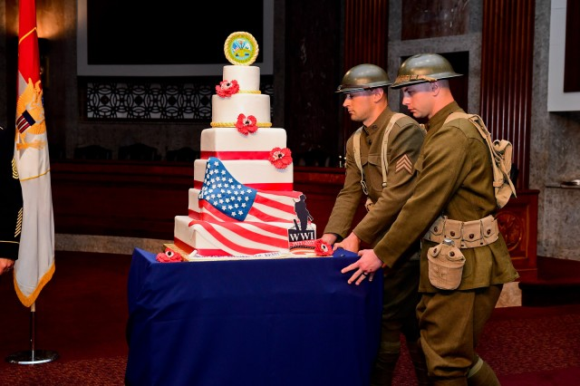 Soldiers dressed in World War I-era uniforms push out the cake for the Army's 242nd birthday celebration at the Senate Dirksen Senate Office Building in Washington, D.C., June 14, 2017.