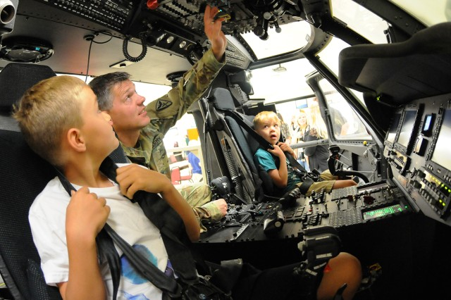 Branson and Kohen Barker, Gold Star Family members, get a flight lesson from CW4 Scott Skaug, Headquarters Headquarters Co., 1-223rd Avn. Regt., in a UH-60M training simulator.