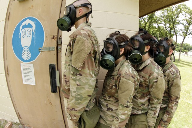 "Wearing gas masks, trainees wait to go into the ""cold room"" of the gas chamber before moving to the ""hot room"" for a lungful of tear gas."