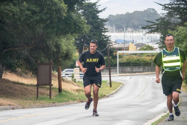 Staff Sgt. Ryan Moorcroft is on the last 100 meters of the five kilometer run during the Platoon Sergeant of the Year competition's physical fitness assessment May 31 at the Presidio of Monterey. At right is 229th Military Intelligence Battalion Command Sgt. Maj. Matt Ruan.