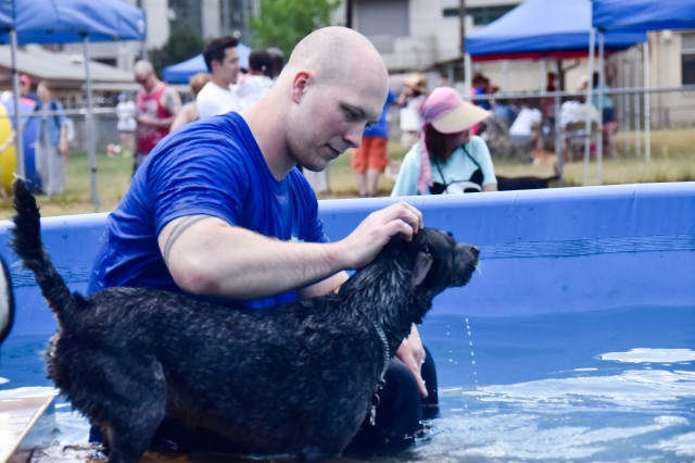 Sgt. James Delucas, an analyst from Marine Corps Forces Korea, plays with a dog in the pet swimming pool installed at the Community Dog Playground, Yongsan Pet Care Center, June 3, during the Pet Expo.