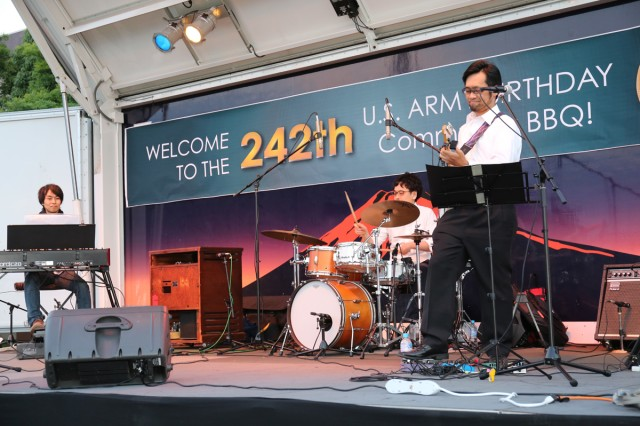 A band, Triangle in March, performs music during the community BBQ night held June 14, 2017 at Camp Zama Yano field as part of the Army Birthday Week. (U.S. Army photo by Noriko Kudo)