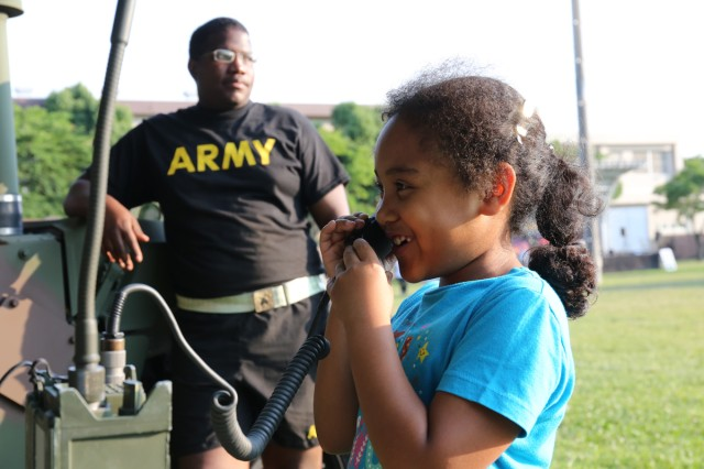 An event participant tries out a Manpack radio displayed during the community BBQ night held June 14, 2017 on Camp Zama's Yano Field as part of the Army Birthday Week. (U.S. Army photo by Noriko Kudo)