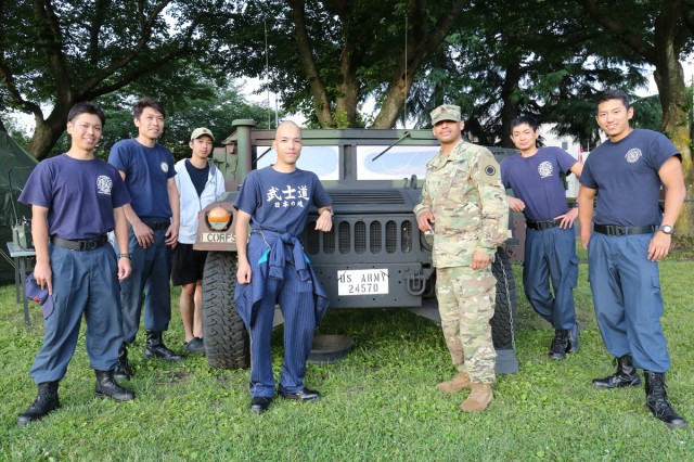 Employees of Directorate of Emergency Services take a photo with a Soldier in front of the displayed military vehicle during the community BBQ night held June 14 on Camp Zama's Yano Field as part of the Army Birthday Week.  (U.S. Army photo by Noriko Kudo)