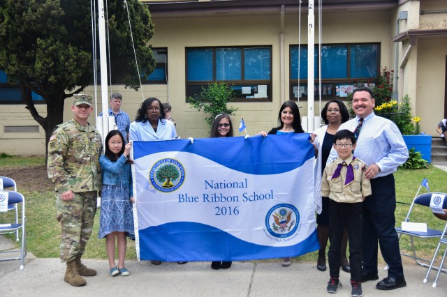 Representatives of Seoul American Elementary School hold up the Blue Ribbon Flag before raising it up the flag pole.