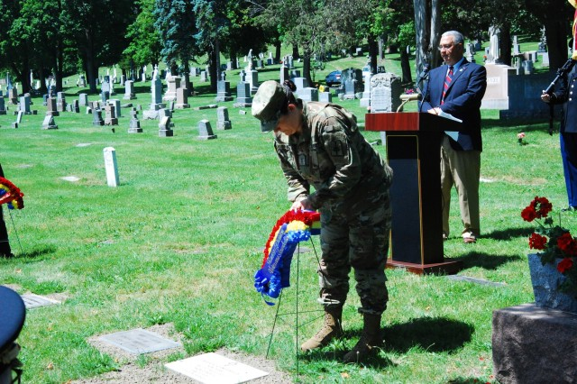 New York Army National Guard Chief Warrant Officer 3 Stephanie Spanton presents a memorial wreath on behalf of the Rainbow Division Veterans Foundation at the graveside of WWII casualty Pfc. Silvio Campanella at the St. Agnes Cemetery in Albany, N.Y. June 14, 2017. The Rainbow Division Veterans Foundation helped coordinate the memorial ceremony and Soldiers of the 42nd Infantry Division Headquarters provided colors and honors.