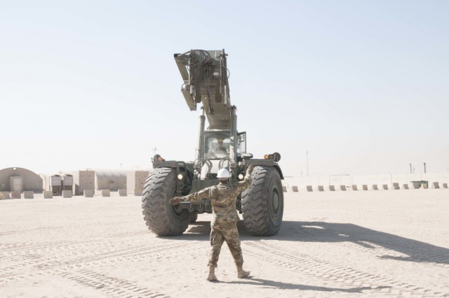 U.S. Army Master Sgt. Edgar Ponce guides Spc. Agnes Torres, both with the 369th Sustainment Brigade, as she drives a Rough Terrain Container Handler (RTCH) at Camp Arifjan, Kuwait, on November 12, 2016. RTCHs are used to move large containers over various types of terrain.