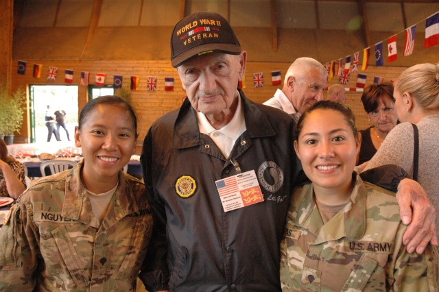 Spc. Amanda Nguyen, left, and Spc. Carmen Cuestas, both of the 29th Infantry Division, pose with retired Master Sgt. Norman Duncan, a World War II Veteran who served with the 29th Infantry Division during the liberation of France, after a ceremony honoring veterans in Carentan, France, June 2, 2017. The ceremony commemorates the 73rd anniversary of D-Day, the largest multi-national amphibious landing and operational military airdrop in history, and highlights the U.S.' steadfast commitment to European allies and partners. Overall, approximately 400 U.S. service members from units in Europe and the U.S. are participating in ceremonial D-Day events from May 31 to June 7, 2017. (U.S. Army Photo by Master Sergeant Sean McCollum, 29th Infantry Division Public Affairs)