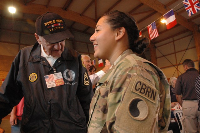 Spc. Carmen Cuestas, a Soldier with the 29th Infantry Division, speaks to retired Master Sgt. Norman Duncan, a World War II Veteran who served with the 29th Infantry Division during the liberation of France, after a ceremony honoring veterans in Carentan, France, June 2, 2017. The ceremony commemorates the 73rd anniversary of D-Day, the largest multi-national amphibious landing and operational military airdrop in history, and highlights the U.S.' steadfast commitment to European allies and partners. Overall, approximately 400 U.S. service members from units in Europe and the U.S. are participating in ceremonial D-Day events from May 31 to June 7, 2017. (U.S. Army Photo by Master Sergeant Sean McCollum, 29th Infantry Division Public Affairs)Spc. Carmen Cuestas, a Soldier with the 29th Infantry Division, speaks to retired Master Sgt. Norman Duncan, a World War II Veteran who served with the 29th Infantry Division during the liberation of France, after a ceremony honoring veterans in Carentan, France, June 2, 2017. The ceremony commemorates the 73rd anniversary of D-Day, the largest multi-national amphibious landing and operational military airdrop in history, and highlights the U.S.' steadfast commitment to European allies and partners. Overall, approximately 400 U.S. service members from units in Europe and the U.S. are participating in ceremonial D-Day events from May 31 to June 7, 2017. (U.S. Army Photo by Master Sergeant Sean McCollum, 29th Infantry Division Public Affairs)