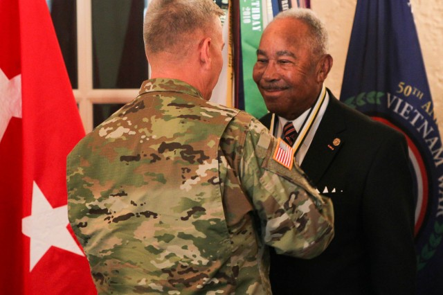 Maj. Gen. Christopher Hughes, commander of U.S. Army Cadet Command and Fort Knox, places a medallion around the neck of Lt. Col. (Ret.) Jona McKee, signifying his induction into the ROTC National Hall of Fame June 14 at Fort Knox.