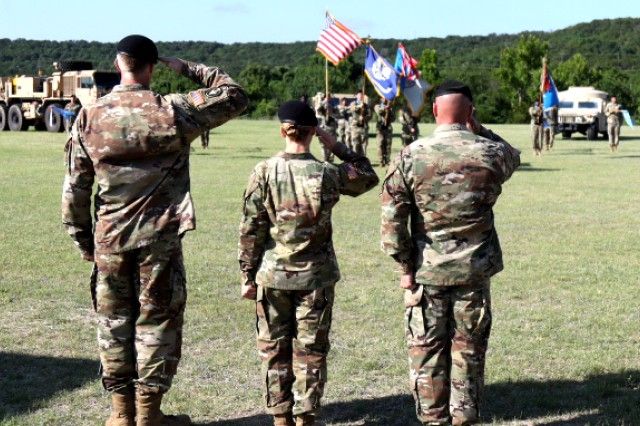 Command Sgt. Maj. Thomas Baird (far left), Col. Laura Knapp (center), and Command Sgt. Maj. Ryan Hipsley (right) salute the National Colors as the National Anthem is played during the 504th Military Intelligence Brigade Change of Responsibility, June 16, at Fort Hood, Texas.
