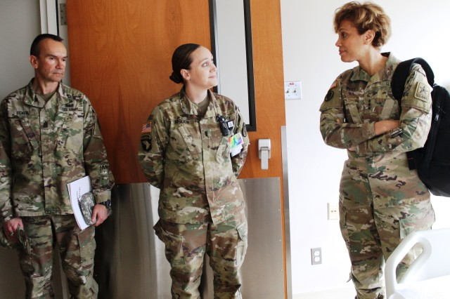 1LT Kimberly Higdon (center) on the Progressive Care Unit, explains the negative pressure room advantages to LTG West and CSM Ecker during their tour of the floor.