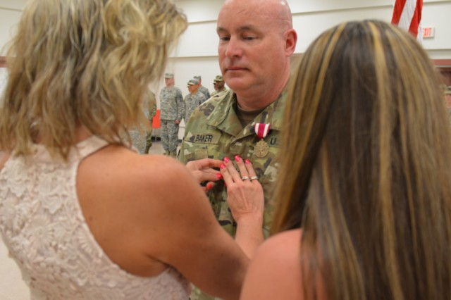 Debbie Baker, wife of Brig. Gen. Matthew Baker, and his daughter Nikki Baker, pin his newly-appointed rank on his chest and hat. Baker was promoted on June 3, 2017, in Darien, Ill. (US Army photo by Spc. Brianna Saville/Released)