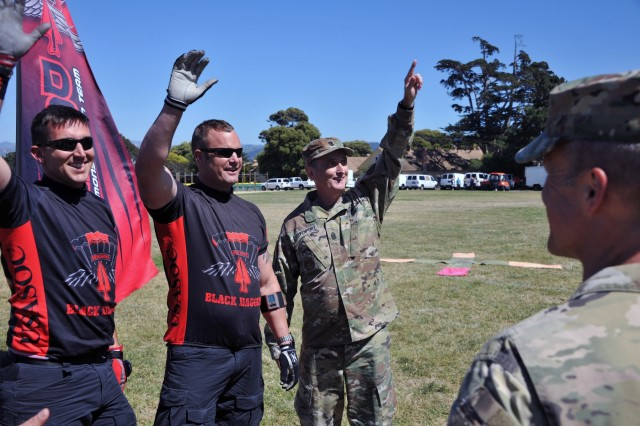Command Sgt. Maj. David Davenport, the senior enlisted leader for the U.S. Army Training and Doctrine Command, waves with the U.S. Army Special Operations Command Black Daggers Parachute Demonstration Team following their jump into the Presidio of Monterey, California, for Resiliency Day June 16. Davenport traveled throughout TRADOC during the week of the U.S. Army's 242nd Birthday and concluded in Monterey where he spoke about NCO development and the Defense Language Institute Foreign Language Center's future role in the Army's 2025-2050 timeframe and beyond. (U.S. Army photo by Patrick Bray/Released)