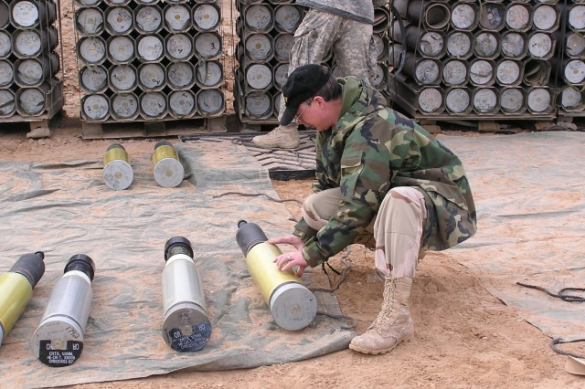 Mike Walsh, Joint Munitions Command Quality Assurance Ammunition Surveillance expert, inspects 120mm ammunition during 'Relief In Place' or 'Transfer Of Authority' effort at Ramadi, Iraq, in 2007.