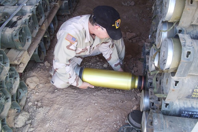 Mike Walsh, Joint Munitions Command Quality Assurance Ammunition Surveillance expert, inspects 120mm tank ammunition in storage during a deployment to Iraq in 2006.