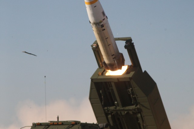The new M57A1 Army Tactical Missile System missile is being fired over the cab of an M142 High Mobility Artillery Rocket System launcher.
