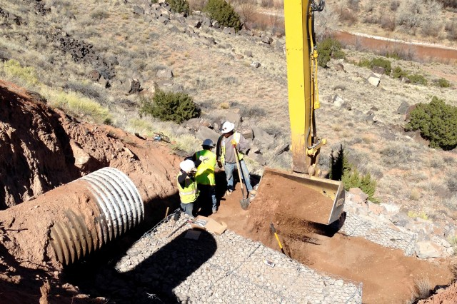 JEMEZ DAM, N.M. -- Due to concerns that moving equipment into the area downslope of the culvert might damage cultural resources, the BLM crew used long-reach equipment from above to repair the culvert, Mar. 2, 2017.
