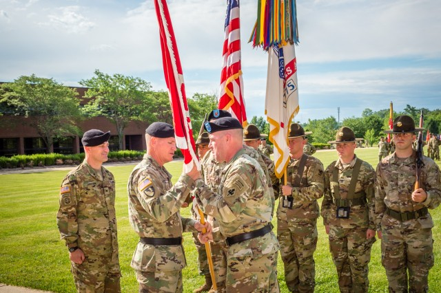 Brig. Gen. James Raymer, former commandant of the U.S. Army Engineer School, passes the regimental colors to Maj. Gen. Kent Savre, Maneuver Support Center of Excellence and Fort Leonard Wood commanding general, during Raymer's relinquishment of commandancy ceremony Friday.