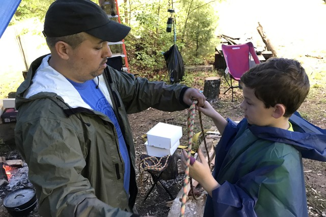 John Bonot helps his son, Shade Bonot, tie a figure eight knot.
