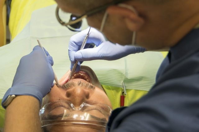 Victor Garcia, a 49-year-old landscaper from El Cenizo, Texas, a colonia next to the Texas-Mexico border, has a few tooth fillings performed June 20, 2017, by Capt. Mark Burns, a Reserve Soldier with the 7226th Medical Support Unit. Burns and other Soldiers are currently participating in an Innovative Readiness Training mission to provide free medical services to economically distressed colonias in the Laredo area.
