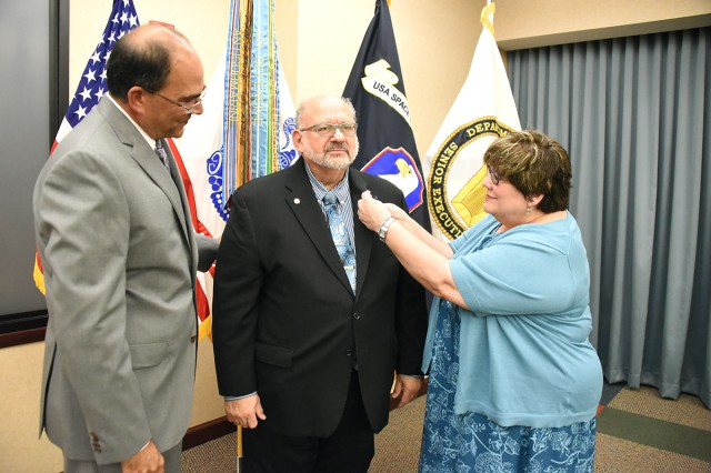 John H. Cummings III, U.S. Army Space and Missile Defense Command/Army Forces Strategic Command public affairs specialist, receives his retirement pin from his wife, Barbara, during his retirement at the command's Redstone Arsenal, Alabama, headquarters June 21. Looking on is Thomas Webber, SMDC Technical Center director, who performed the ceremony. Cummings retires with 42 years of federal service.