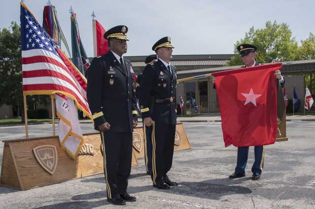 The U.S. Army Operational Test Command's Command Sgt. Maj. Jason Schmidt (right), uncases the Army's newest one-star general officer flag after USAOTC Commander Col. John C. Ulrich (center) is promoted to brigadier general June 23. Lt. Gen. (Retired) Michael E. Williamson (left), who completed more than 34 years of service culminating as the Military Deputy/Director, Army Acquisition Corps, Office of the Assistant Secretary of the Army (Acquisition, Logistics and Technology), Washington, D.C., hosted the promotion ceremony
