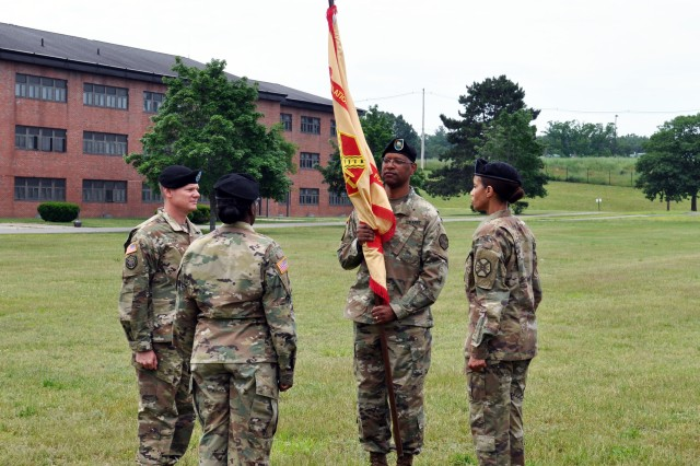 Lt. Col. Efrem Z. Slaughter, incoming garrison commander, holds the colors during the June 23 change of command ceremony at U.S. Army Garrison Fort Devens/Devens Reserve Forces Training Center. From left are Col. Martin F. Klein, ASA-Fort Dix commander; Lt. Col. Charlette K. Woodard, outgoing garrison commander; and Fort Devens Command Sgt. Maj. Tammy Harris.