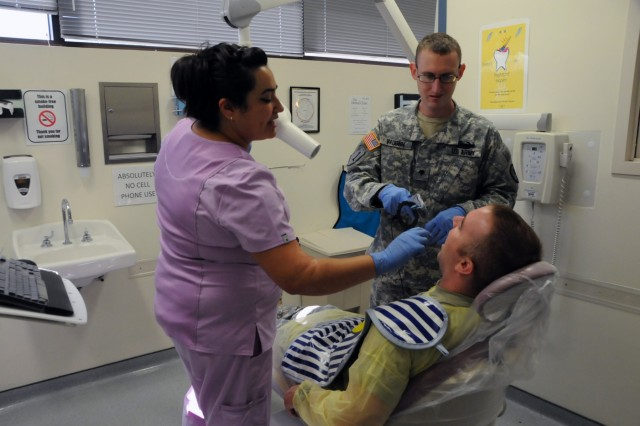 Spc. Andrew Vaughn, a dental assistant assigned to 7246th Medical Support Unit located in Elkhorn, Nebraska, learns how to take dental x-rays from staff member Mari Pasman, a dental assistant on the team.  Vaughn is one of approximately 25 U.S. Army Reserve Soldiers who are working in partnership with Rosebud Indian Health Service to provide medical care to the local tribal population.