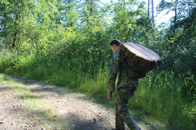 A Soldier assigned to 1st Special Forces Group (Airborne) carries a log of wood during the Group's 60th Anniversary round-robin training event at Joint Base Lewis-McChord on June 23. 1st Group veterans rucked with the Soldiers or manned six stations, each focusing on a decade of the Group's history. Soldiers who answered historical questions correctly removed weight from their rucksacks; Soldiers who missed questions added extra weight to their packs.