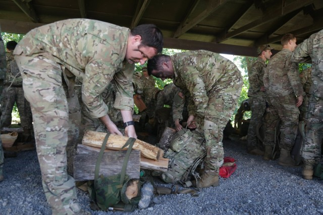 Two Green Berets assigned to 1st Special Forces Group (Airborne) pack their rucks with wood prior to beginning the 60th Anniversary round-robin training event June 23 at Joint Base Lewis-McChord. The round-robin training event involved Soldiers and veterans rucking to six stations, each representing a decade in the Group's history.