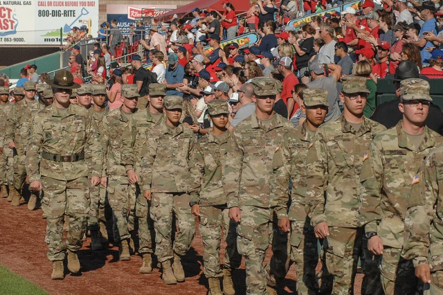 Staff Sgt. Chad Hickey, Fort Leonard Wood Drill Sergeant of the Year, left, leads a procession of Soldiers along the first-base line as fans cheer Saturday at Hammons Field during Military Appreciation Day.