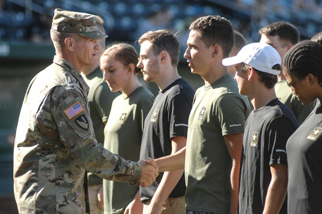 Maj. Gen. Kent Savre, MSCoE and Fort Leonard Wood commanding general, congratulates Springfield-area inductees after completing an Oath of Enlistment ceremony Saturday at Hammons Field in Springfield, Mo.