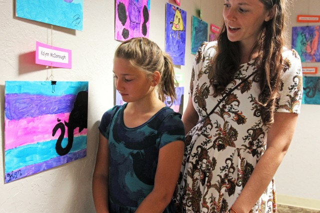 Kalynn McDonough, age 10, shows her mother, Amanda, the art she produced that was chosen for the show's poster. Artists could produce works in three themes: an elephant, the peace sign, or a monster.