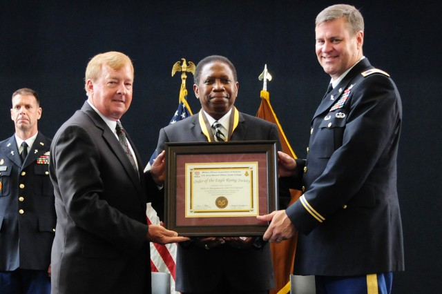Retired Air Force Lt. Col. Dana Atkins, Military Officers Association of America president and chief executive officer, and Col. Garry L. Thompson (right), U.S. Army Warrant Officer Career College commandant, induct retired CW5 Rufus N. Montgomery Sr. into the Order of the Eagle Rising Society during a ceremony at the U.S. Army Aviation Museum June 26.